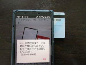 3.マイナンバーカードの番号が書かれた面を写真のようにスマホにピッタリと付ける。